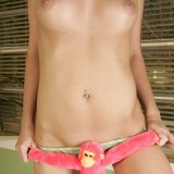 A topless Daisy plays around with her stuffed monkey